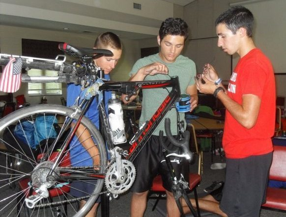Michael JeanFavre of Litchfield, Ct., left, Nic Giraldo-Wingler of Robbinsville, N.J., and Kevin Levi-Goerlich of Columbia, Md., make repairs to a bicycle in the parish hall of St. James Episcopal Church. Photo Credit: Knoxville News Sentinel